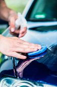 Close-up of male hands waxing the surface of a blue car at auto wash poster
