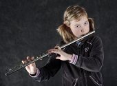 Attractive young girl flautist, flutist holding flute. Studio shot, black background.