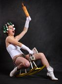 Screaming militant feminist with rolling pin ridden on a wooden hobby horse. Humorous image. Great f