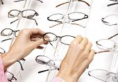 Closeup of a females hands pulling glasses from display rack poster