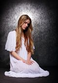 Romantic style picture young beautiful girl dressed in white shirt tunic with glory (halo) over her head. Conceptual image.