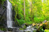 Beautiful waterfall in green forest. Scenery from Novohradske Hory - mountains in Czech Republic - E