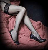 Beautiful slim legs in black nylons on a pink background. Vintage style photography - great for cale