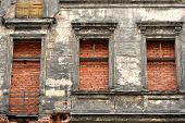 old tenement with windows and door filled with bricks - close up poster
