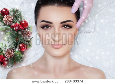 poster of A Beautiful Woman Gets A Facial Massage In The Spa Salon. Closeup Of Woman's Face And New Year Wreat