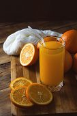 A Glass Of Orange Juice, Cut Into Pieces Orange, Oranges On A Wooden Board, Dark Background. Beautif poster