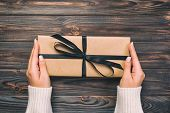 Woman Hands Give Wrapped Valentine Or Other Holiday Handmade Present In Paper With Black Ribbon. Pre poster