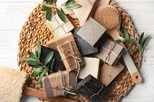 Wicker Mat With Handmade Soap Bars, Brush And Olive Leaves On Table, Top View poster