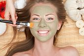 Close-up of young beautiful woman with clay facial mask at spa salon