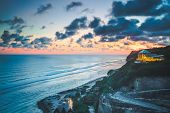 Overview ocean, cliff, hotel. Sunset landscape, Bali. Gorgeous scenery the colorful sunset cloudy sk poster