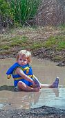 Toddler Girl Playing In Mud Puddle