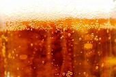 Background from a surface of beer with a sun beam