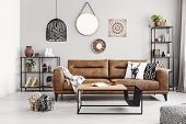 Leather Sofa With Pillows And Blanket In The Middle Of Elegant Living Room Interior With Metal Shelv poster