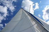 Yacht sail and mast with white cloudless and blue sky in the background