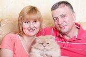 A happy family enjoying their free time at home with fluffy cat poster