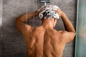 Rear View Of Man Washing Hair With Shampoo And Taking Shower poster