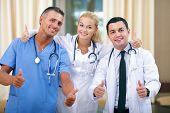 Постер, плакат: Счастливый команда врачей показывая большие пальцы руки вверх