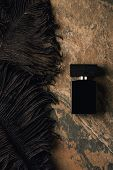 Top View Of Perfume Bottle And Decorative Black Feathers On Brown Weathered Surface poster