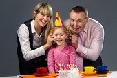 picture of ear candle  - Happy family pulling on their daughter - JPG