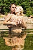 Beautiful Naked Couple Kissing In The Water Outdoors.