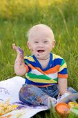 picture of face painting  - Little baby boy with Down syndrome painting finger paints on white paper with a smile - JPG
