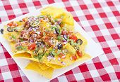 Cheesy Nachos On A Red Checkered Tablecloth