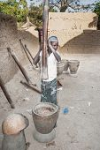 Young Woman Working With Typical And Rudimentary Wooden Mortar, Mali, Africa.