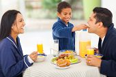 cute little indian boy feeding his father fruit on breakfast table