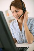 Young woman at work talking on phone with headset