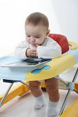 Cute little baby walking in walker playing with tablet