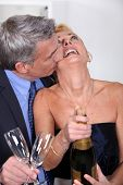 Couple popping a champagne cork