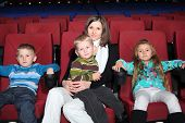 Happy mother with children in the cinema