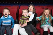 Mother with children with admiration watching a movie in the cinema