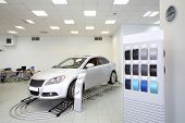 New shine car stands in office of shop selling cars near stand with samples of paint for body.