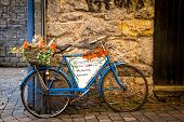 stock photo of ireland  - Old blue bicycle leaning against a stone wall in Galway - JPG