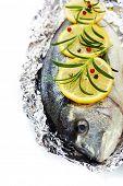 pescado fresco de la dorada con tomillo y limón sobre blanco - comida y bebida de la frontera