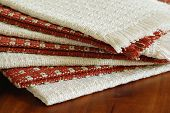 Stack of homespun cotton napkins in natural and cinnamon colors on wooden table.  Macro of texture a