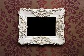Elegant wooden frame with Victorian style wallpaper as background.