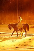 woman in medieval dress riding horse on beach at sunset