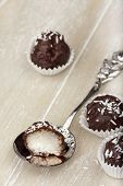 stock photo of bittersweet  - With bittersweet chocolate covered coconut milk rice truffles and a silver spoon with a halved truffle on a wooden tray - JPG