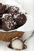 stock photo of bittersweet  - With bittersweet chocolate covered coconut milk rice truffles in a half coconut shell and a silver spoon on a wooden tray - JPG
