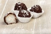 stock photo of bittersweet  - Three and a halved coconut milk rice with bittersweet chocolate covered truffles on wood - JPG