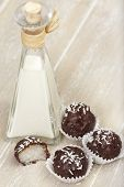 picture of bittersweet  - With bittersweet chocolate covered coconut milk rice truffles and a bottle of coconut cream on a wooden tray - JPG