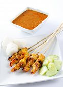 Chicken satay, skewered and grilled meat, served with peanut sauce, cucumber and ketupat. Traditiona