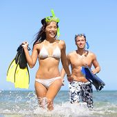 Beach couple having fun on vacation travel with snorkel, mask and fins. Happy interracial multi-ethnic young couple running excited at tropical beach during summer holidays at Maui, Hawaii, USA
