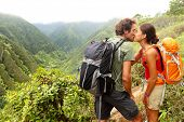 Couple in love kissing while hiking on Hawaii. Romantic young couple hikers during hike in beautiful mountain forest nature. Healthy lifestyle multi-ethnic couple on Waihee ridge trail, Maui, USA
