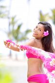 Natural beauty ethnic woman happy on beach waving pink scarf in joy. Beautiful joyful girl on summer vacation travel holiday on Big Island, Hawaii, USA. Gorgeous pretty mixed race female bikini model.