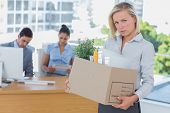 Upset businesswoman leaving office after being let go carrying cardboard box