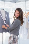 Attractive fashion designer measuring blazer lapel and looking at the camera