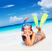 Happy diver woman lying down on beautiful sandy beach, wearing goggles, tube and flippers, having fun on summertime resort, active lifestyle, water discovery concept